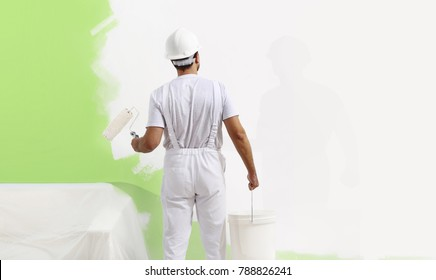 painter man at work with a paint roller, wall painting green color ecological concept, web banner template
