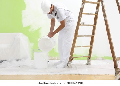 painter man at work pour into the bucket color for painting the wall