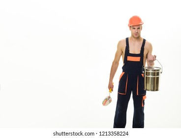 Painter man at work with roller, bucket. Painter concept. House renovation. Construction worker with painter roller&bucket. Professional workman in hardhat. Sexy muscular man hold paint roller. Repair