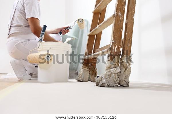 Maler auf der Arbeit mit einer Walze, Eimer und Leiter, Bodenansicht