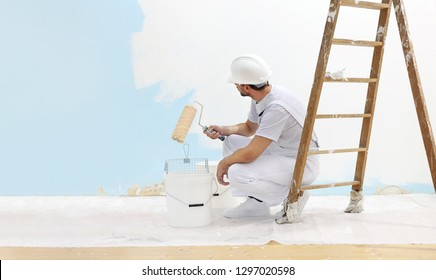 painter man at work takes the color with paint roller from the bucket and look the wall, copy space template
