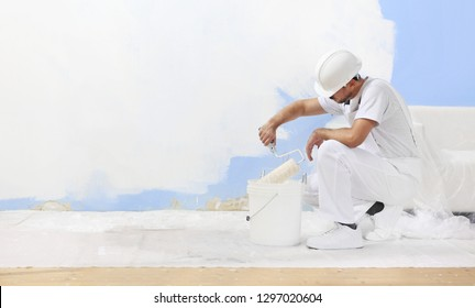 painter man at work takes the color with paint roller from the bucket, blank white wall for copy space