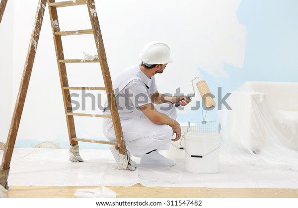 painter man at work takes the color with paint roller from the bucket