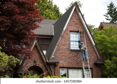 Painter on a ladder painting the windowsill of an old brick house, in a home repair scene with space for text on the left