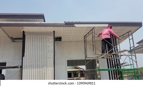 The painter on the scaffolding is painting the eaves of the house.