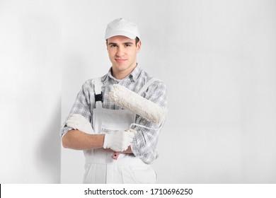 Malerin in Overalls, die eine Farbwalze halten, wie er vor einer neu gestrichenen weißen Wand in einem Bau-, Bau- oder Wohnungsverbesserungskonzept mit Kopienraum steht