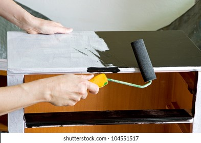 painter with paint roller painting a wooden commode