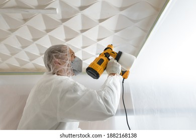 The painter is painting a 3d ceiling with a spray gun.
