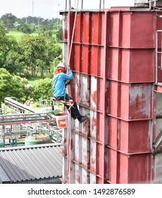 The painter are painting the factory wall Red Oxide Primers. The painter uses a rope to rappelling for the paint.