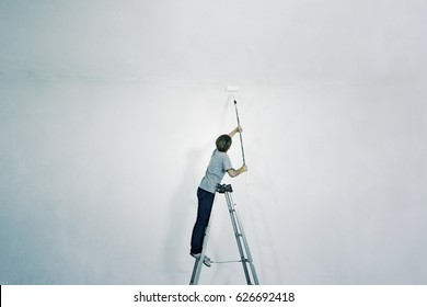 Painter painting on a white wall