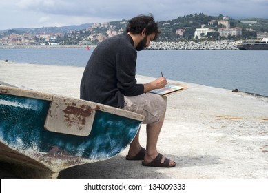 Painter painting a picture sitting on old row boat on the pier