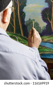 Painter painting picture in workshop rear view