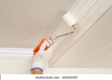Painter paints the ceiling using a roller