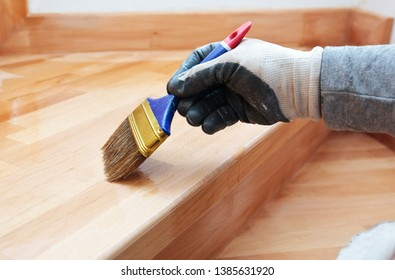 Painter paints a varnish wooden board by brush
