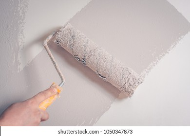 The painter paints the wall with a fur roller, a backdrop, a background