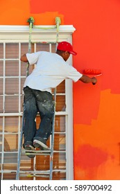 Painter paints wall orange in Cape town