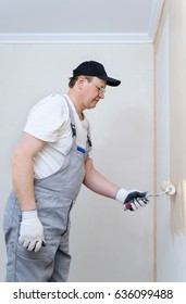 Painter paints a wall in the room. He holds in  hand roller.