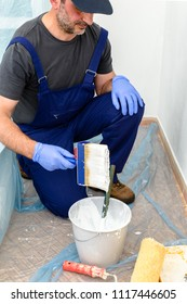 Painter paints the wall with the tint of white. Wall with serious moisture problems. Detail of the brush. white dye is prepared for the painter's job.