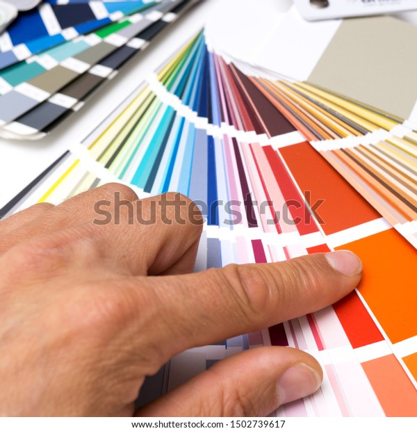 Painter picks wall paint from colorful color fan