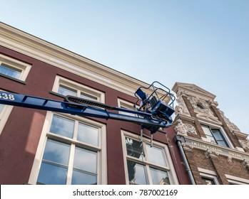 Painter in platform maintaining old building. Deventer, Overijssel, Netherlands.