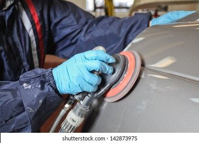 Painter polishes a car body component