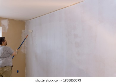 The painter primed the wall with a primer repair the wall after applying gypsum plaster on using paint roller brush