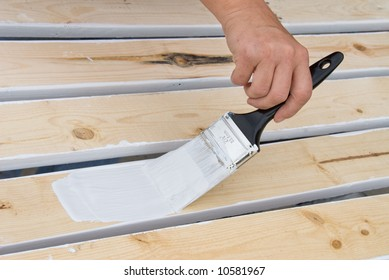 A painter primes the wooden slats of a fence that is being constructed.
