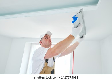 Painter with putty knife. Plasterer smoothing ceiling surface at home renewal