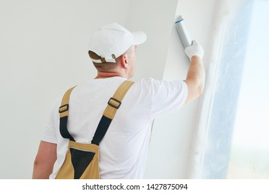 Painter with putty knife. Plasterer smoothing esconson surface at home renewal