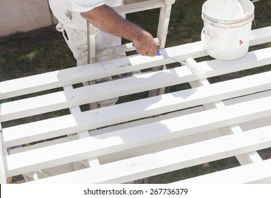 Painter Rolling White Paint Onto The Top of A Home Patio Cover.
