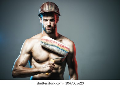 Painter. Sexy muscular unshaven man holds paint roller. Man worker in hard hat. Room painting job. Painter contractor in protective helmet. Man worker. Construction. Copy space for advertise tool shop