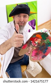 Painter sitting in front of an easel and looking at the camera