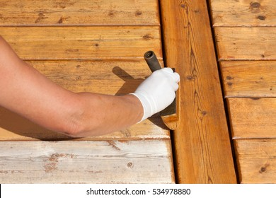 Painter staining deck boards with transparent protective outdoor decking paint applying stain with brush
