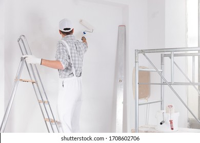 Painter standing on a ladder painting a white wall in a room under construction leaning away using a roller viewed from the rear with interior scaffolding frame alongside