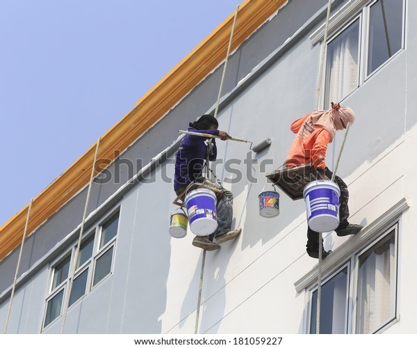 Painter Uses Paint Roller Outside High Stock Photo (Edit Now