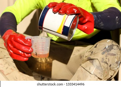 Painter using red chemical glove safety protection pouring harder into  measuring cup
