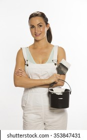 Painter wearing bib & braces overall holding brush