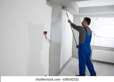 Painter wearing bib overalls painting house interior.