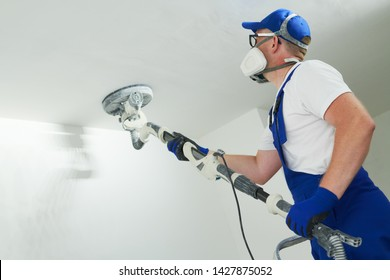 Painter work with ceiling. polishing and sanding the surface after putty for painting