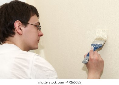 Painter worker at decoration work painting a wall with brush