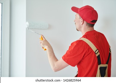 Painter worker with roller painting wall surface into white