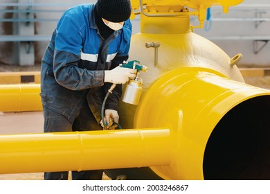 A painter in working clothes paints a metal shut-off valve for gasification from a compressor gun on a summer day. Professional painting of parts. Industrial background.