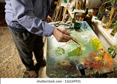 Painter working at palette in studio