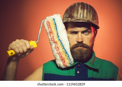 Painter at workplace. Repair, building and home concept - serious bearded man with paint roller. Interior working. Confident handsome painter, craftsman in uniform painting wall in room, making reform