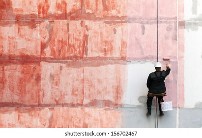 Painter works on the outer building wall with red priming paint