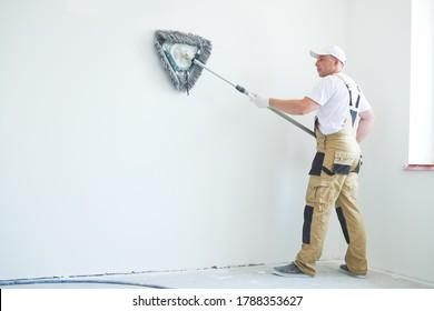 Painter trabaja con una herramienta de limpieza de paredes secas triangulares. Preparación de superficie para la pintura