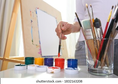 painter's hand holds brush on the background of easel and paints
