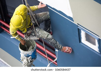 painters hanging on roll, painting color on building wall. Young worker with roller brush, working on high building construction with lift rope belt in city.