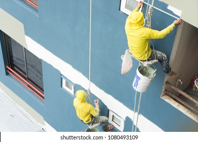 painters hanging on roll, painting color on building wall. facade builder worker with roller brush, working on high building. safety construction with lift rope belt in city.