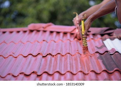Painters paint the old roof tiles red.
